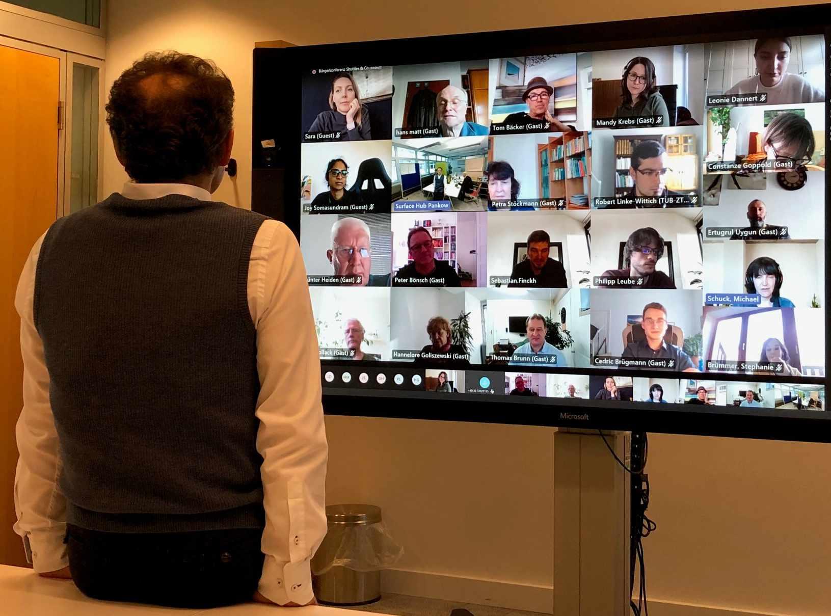 Moderator von re:member vor der Videowand mit den Bürgerkonferenz-Teilnehmern